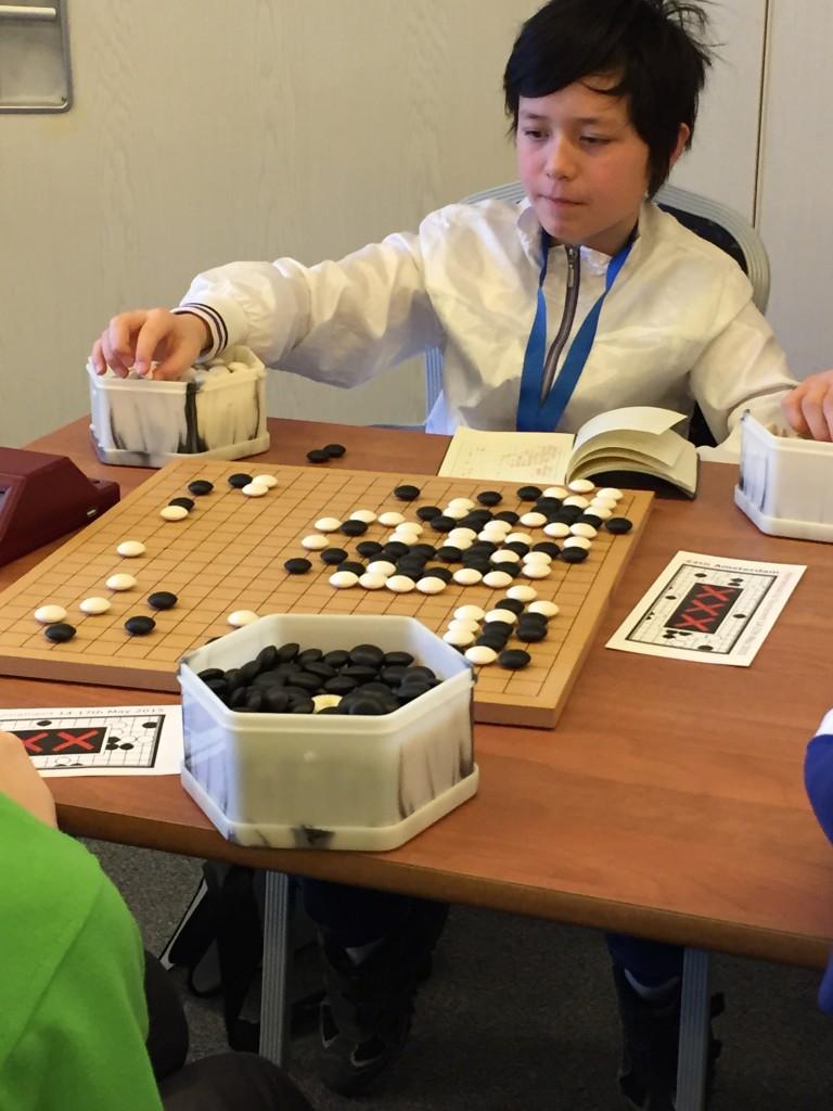Эмануэль Шааф, 5 кю, 12 лет. Германия. Записывал все свои игры в японский блокнот до последней постановки. Он проиграл важнейшую для себя игру против россиянина, в самом конце забыв защититься от двойного атари. При том, что рассчитывал сложные операции в ходе игры.