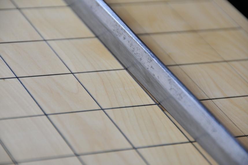 Лезвие меча на поверхности доски